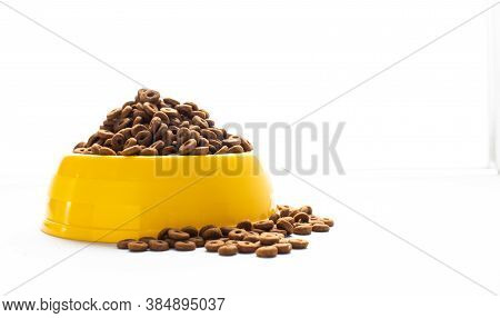 Yellow Plastic Bowl Full With Dry Dog Food Isolated On White Background. Top View Grain Pet Food Wit