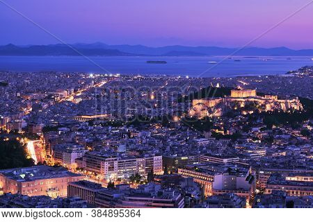 Panoramic View Of Athens And Acropolis Shot From Lycabettus Hill. Parthenon Lit Up By Night Lights.