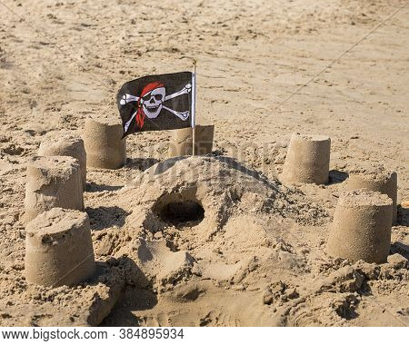 Tourism 2020, Beach Season. Children's Figures Built From Sand Are Decorated With Pirate Flag. Conse