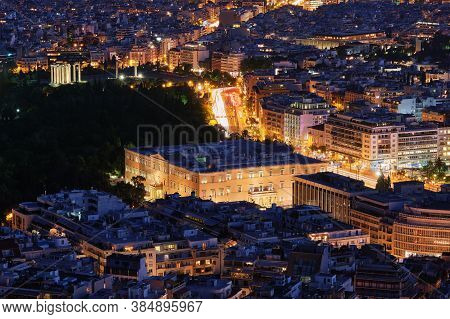 Night View Hellenic Parliament In Syntagma Square Brightly Lit Up And Ruins Of Temple Of Olympian Ze