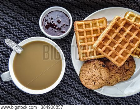 Homemade Cakes, Instant Coffee With Milk, Raspberry Jam On A Black Knitted Background. Waffles And O