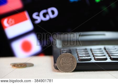 Twenty Cents Singapore Coin On Obverse (sgd) With Black Calculator And Digital Board Of Currency Exc