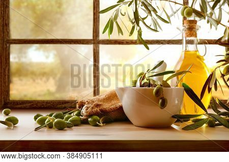 Natural Olive Oil From Organic Harvest On Wooden Table In Front Of Window Of Rural House With Field
