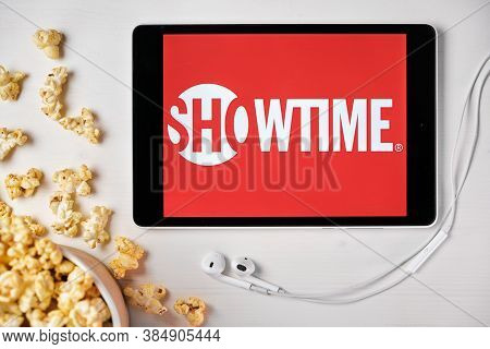 Showtime Logo On The Tablet Screen Laying On The White Table With Scattered Popcorn And Apple Earpho
