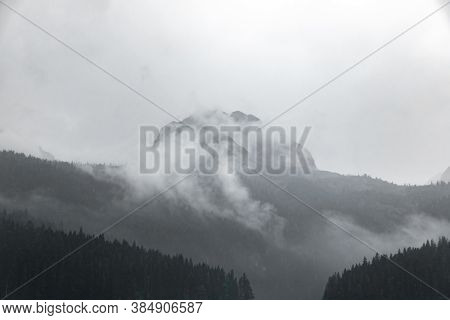 Black And White Photo Of A High Rocky Mountain In The Clouds