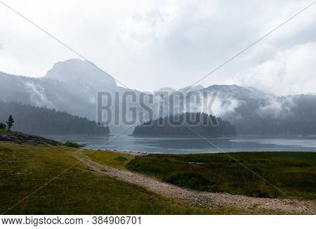 Black Deep Lake Of Glacial Origin Against The Background Of The High Rocky Mountain Zabljak, Montene