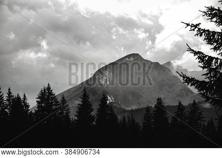 High Mountain In The Clouds Against The Background Of Trees, Black And White Epic Photo
