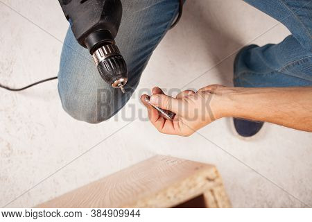A Man Drills A Hole In The Cupboard. A Euro-shunup, Screw-screed For A Wood Chip Slab.