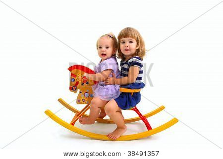 Two Cute Little Girls Riding On A Toy Wooden Horse Isolated On W
