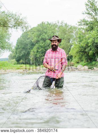 Keep It Reel. Summer Weekend. Fly Fishing. Mature Man Fly Fishing. Man Catching Fish. Happy Bearded