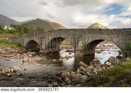Old Stone Arch Bridge Over A Mountain River At Sligachan On The Isle Of Skye In The Highlands Of Sco