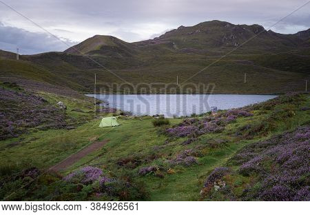 Early Morning At Loch Langaig On The Isle Of Skye, Scotland. Wild Camping In Nature Among Blooming P