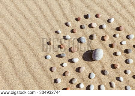 Pattern Of Colored Pebbles In The Shape Of A Circle On Clean Sand. The Concept Of Serenity And Medit