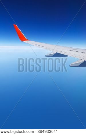 Airplane Wing With A Red Wingtip Against A Clear Blue Sky