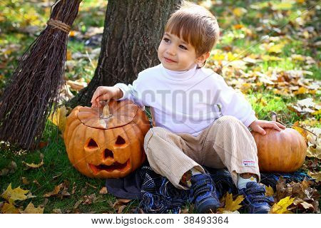 Little Smiling Boy With Two Halloween Pumpkins And A Broom Sitting Near A Tree