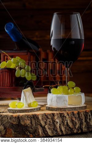 Vertical Image With Cheese Camembert, Grapes And Wine On Wooden Board