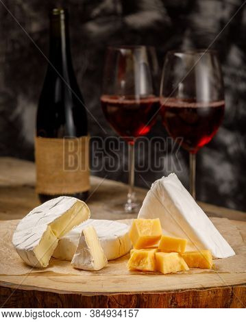 Vertical Image With Cheese Camembert, Brie, Parmesan And Wine On Wooden Board
