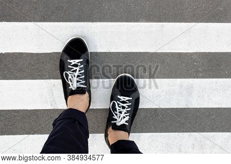 Feet In Sneakers On A Pedestrian Walkway, White Stripes On The Road On The Asphalt, Feet Cross The R