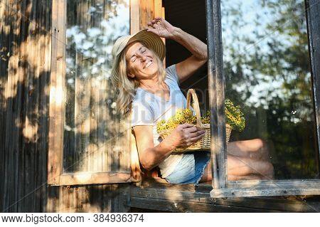 Happy Smiling Elderly Woman Having Fun Posing By Open Window In Rustic Old Wooden Village House In S