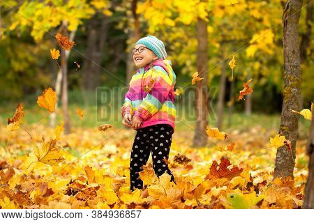 Autumn Background. Fallen Leaves. Small Girl Throws Up Yellow Leaves And Laughts. Child Wearing Colo