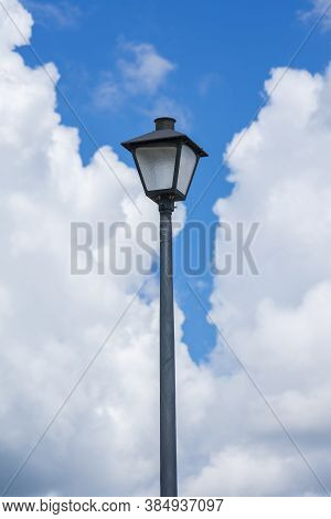 Vertical Shot Of A Lamppost Against A Blue Cloudy Sky.