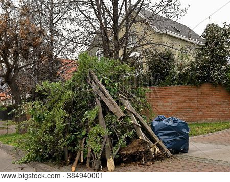 A Pile Of Graden Debris In Front Of A House In A Residential Area