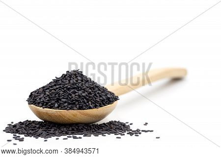 Black Sesame Seed In Wooden Spoon And Piles Sesame Seeds On White Background.