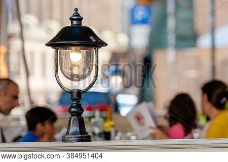 Riga, Latvia - August 16, 2019: Street Cafe Decorated With Lanterns And Plants, Defocused Tables Wit