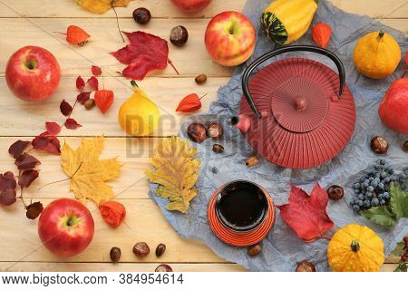 Autumn Tea Party.thanksgiving Day. Red Teapot, A Cup Of Tea, Apples,pumpkin, Chestnuts And Autumn Le