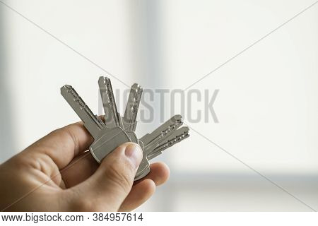Mens Hand Holding A Set Of Keys. Realtor Is Giving The Keys To An Apartment To Clients. Focus On The