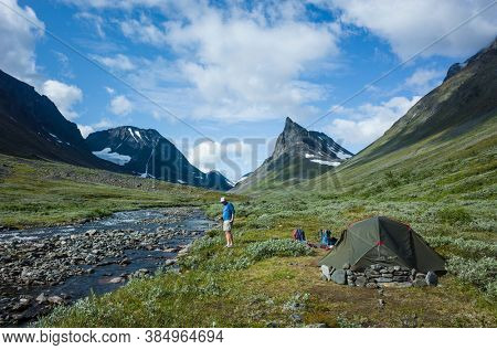 Hiking in Swedish Lapland. Tent on beautiful camping spot next to river with view of Nallo mountain in northern Sweden. Arctic nature of Scandinavia in summer day