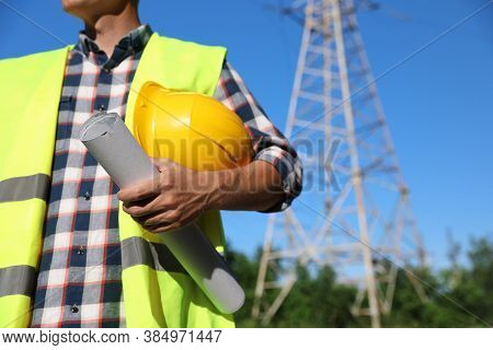 Professional Electrician With Drafting And Helmet Near High Voltage Tower, Closeup