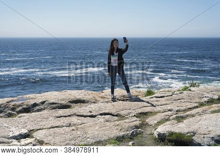 A Chinese Woman Taking A Selfie Outside On The Rocky Coast Of Maine At Pemaquid Point Lighthouse Par