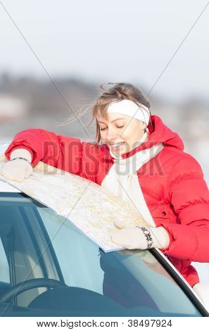 Beautiful Woman Near Car Holding Map In Winter.