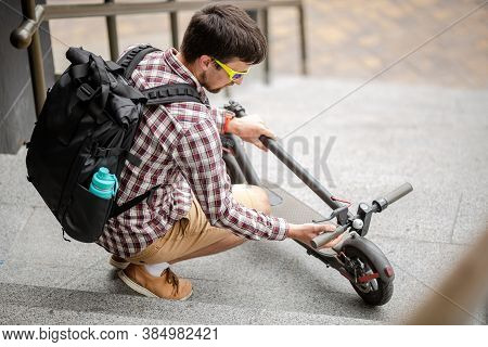 Young Caucasian Man In Casual Clothes With A Backpack Carries A Folded Electric Scooter In His Hand
