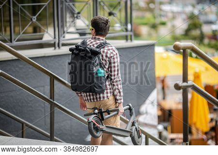 Man Carrying Folded E-scooter In Hand On Stairs Near Building. Moving By Eco Urban Transport, Modern