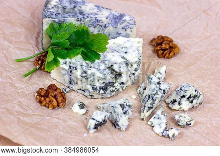 Slices And Triangles Of Danish Blue (dorblue) Cheese With Mold On Light Background.