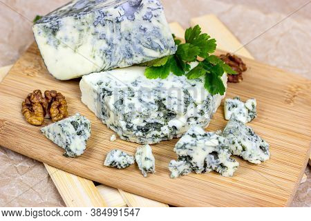 Slices And Triangles Of Danish Blue (dorblue) Cheese With Mold On Wooden Board Background.