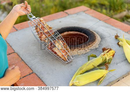 Hands Of A Caucasian Woman Cooks Meat In A Tandoor. Skewers In The Tandoor. Cooking Meat Kebab In A