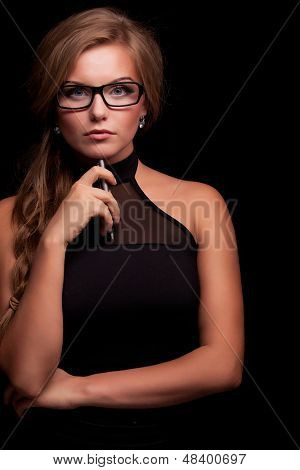Pretty woman giving suspicious look in glasses on black background