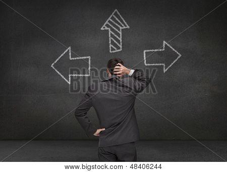 Thoughtful businessman looking at three arrows drawn on chalkboard