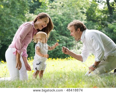 Portrait of a happy family with child giving flower to father int he park poster