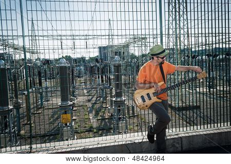 Young musician playing bass guitar with power station background poster