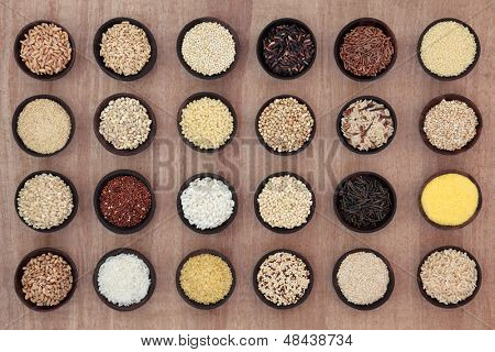 Large grain and cereal selection in wooden bowls over papyrus parchment background.