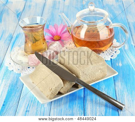 Tasty halva with tea on table poster