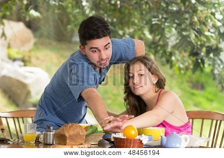 couple having breakfast fighting at home with garden in the background