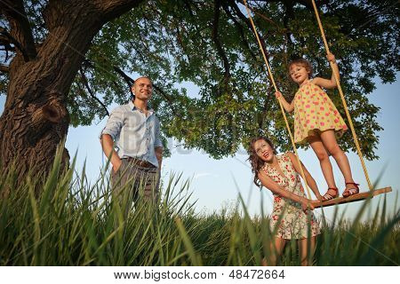 Beautiful girl on the swing in the forest with her parents