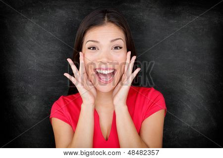 Woman by blackboard / chalkboard excited happy screaming with joy your message with copy space for text. Beautiful young asian multiracial causal female in red on black background.