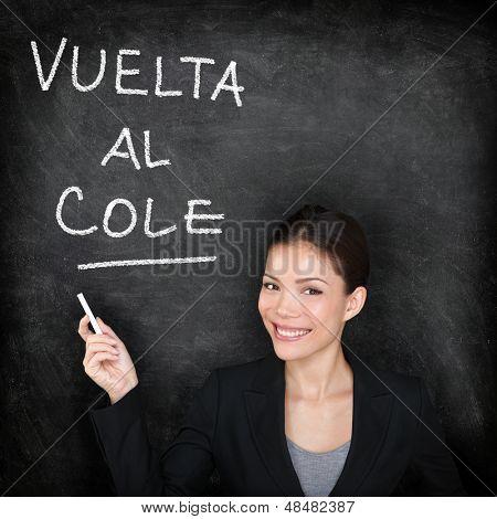 Vuelta al cole - Spanish teacher woman. Back to School written in Spanish on blackboard by female on chalkboard. Woman professor teaching Spanish language at university, high school or primary school.