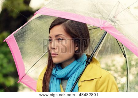 Melancholia - Melancholic woman in rain under umbrella looking sad unhappy and thoughful. Pretty girl walking under a transparent umbrella on rainy fall autumn day. Multiracial female in her 20s.